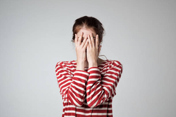 pretty caucasian girl covers her face with her hands - fear stock photos and pictures