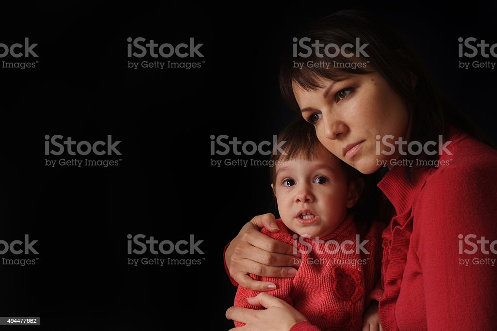 Pretty Caucasian mama with a sad crying daughter stock photo