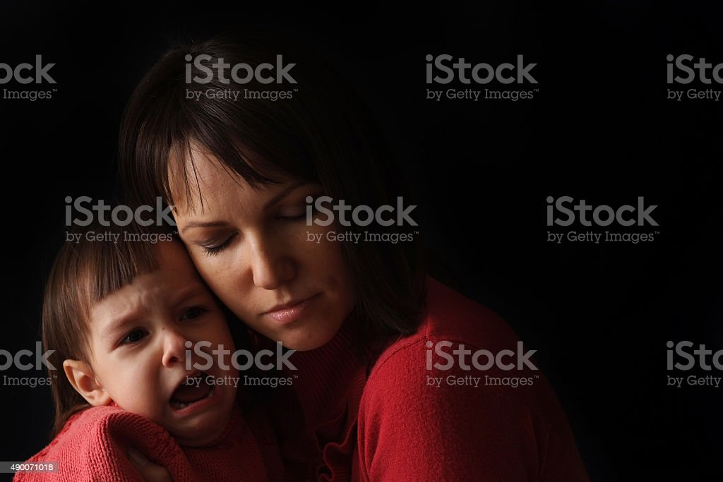 pretty Caucasian mother with a sad crying daughter stock photo
