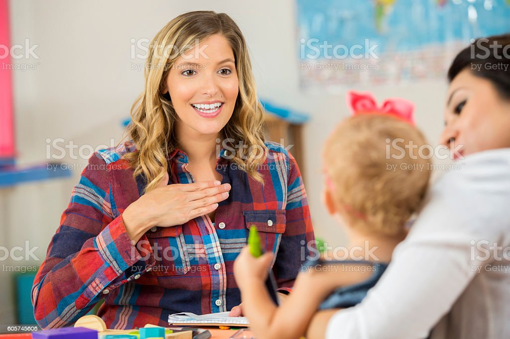 Pretty Caucasian teacher showing a preschooler sign language stock photo