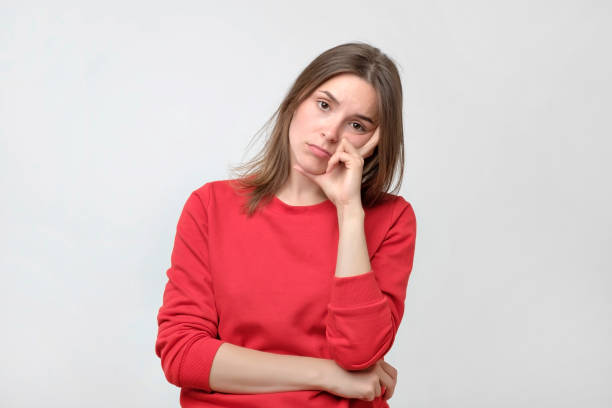 Pretty caucasian woman in red sweater is tired or bored. She do not want to work or study stock photo