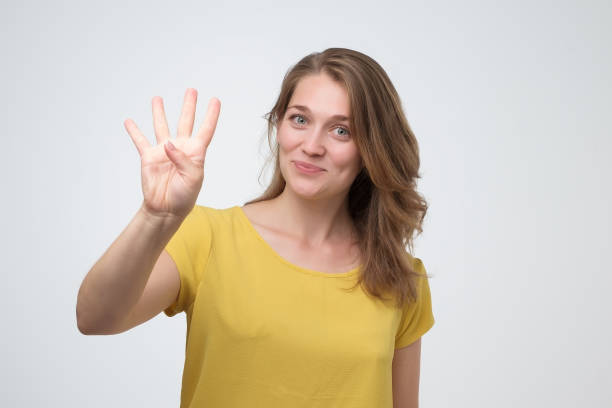 Pretty caucasian young woman holding up four fingers stock photo