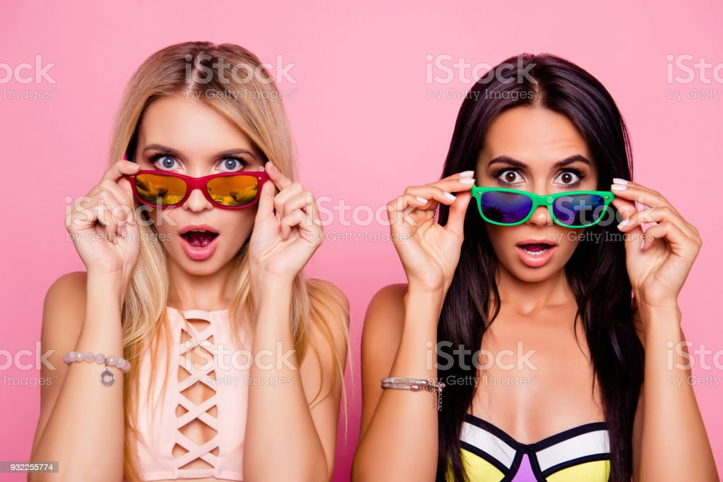 WTF! Pretty, charming, astonished, frustrated impressed, stressed, depressed ladies, tourists looking out glasses with wide open eyes and mouth, holding eyelets with hands, isolated on pink background royalty-free stock photo