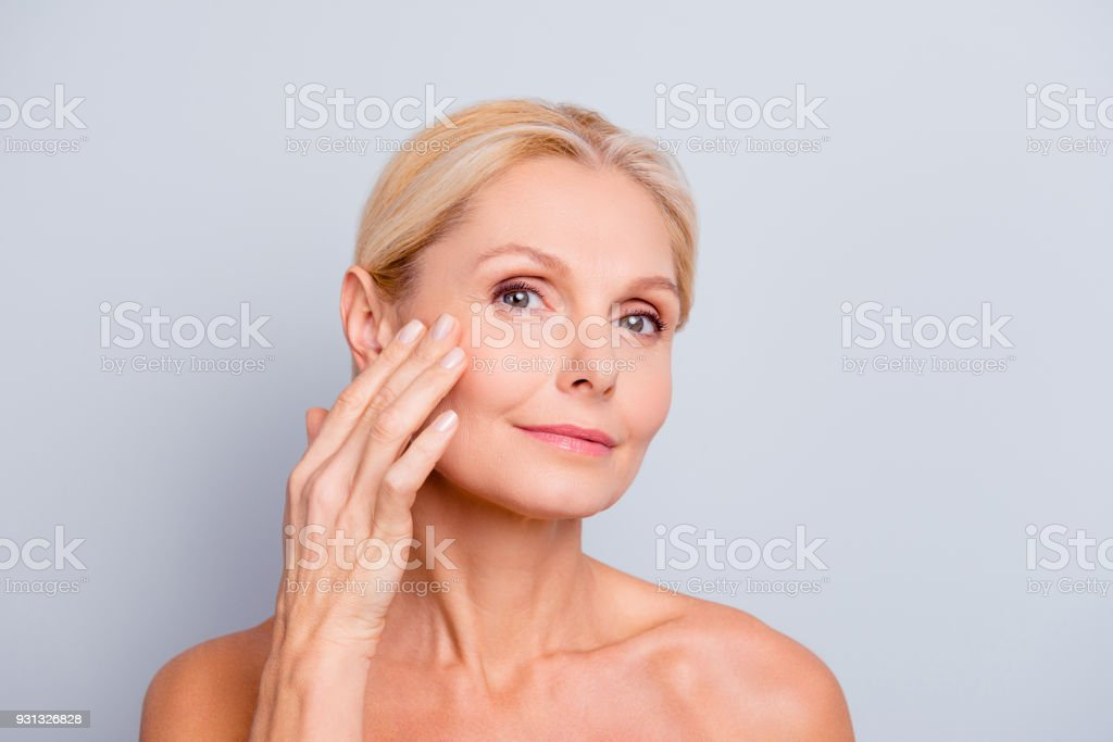 Pretty, charming, attractive woman touching, enjoying her perfect face skin, holding fingers on cheek, pimple, whelk, pustule, dry, oiled, problem skin concept, isolated on grey background stock photo