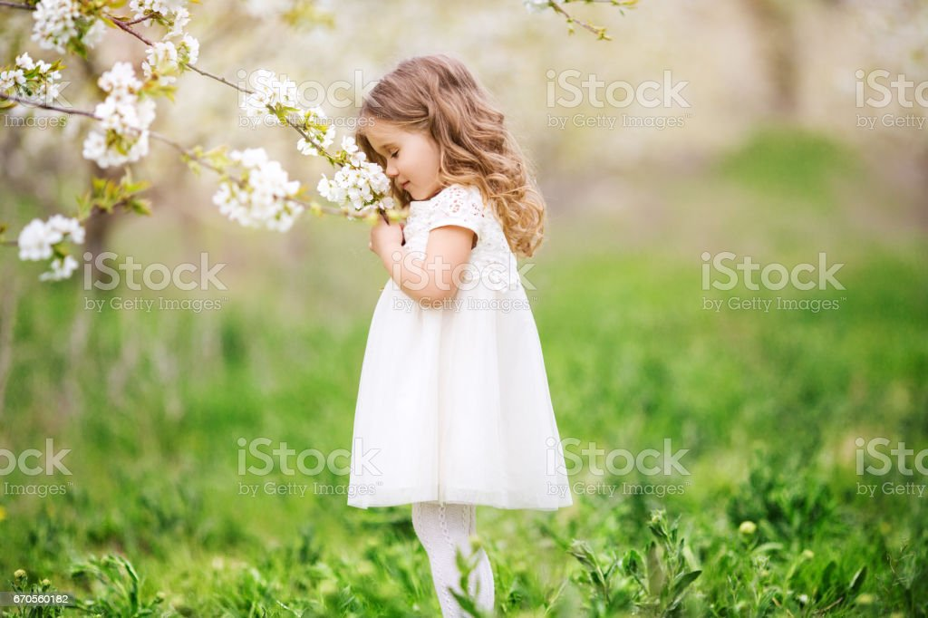 Pretty child girl in blossom garden stock photo