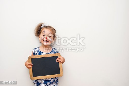 istock Pretty Child Holding A Blackboard 487095344