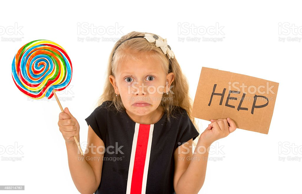 pretty child holding lollipop and help sign in sugar excess stock photo