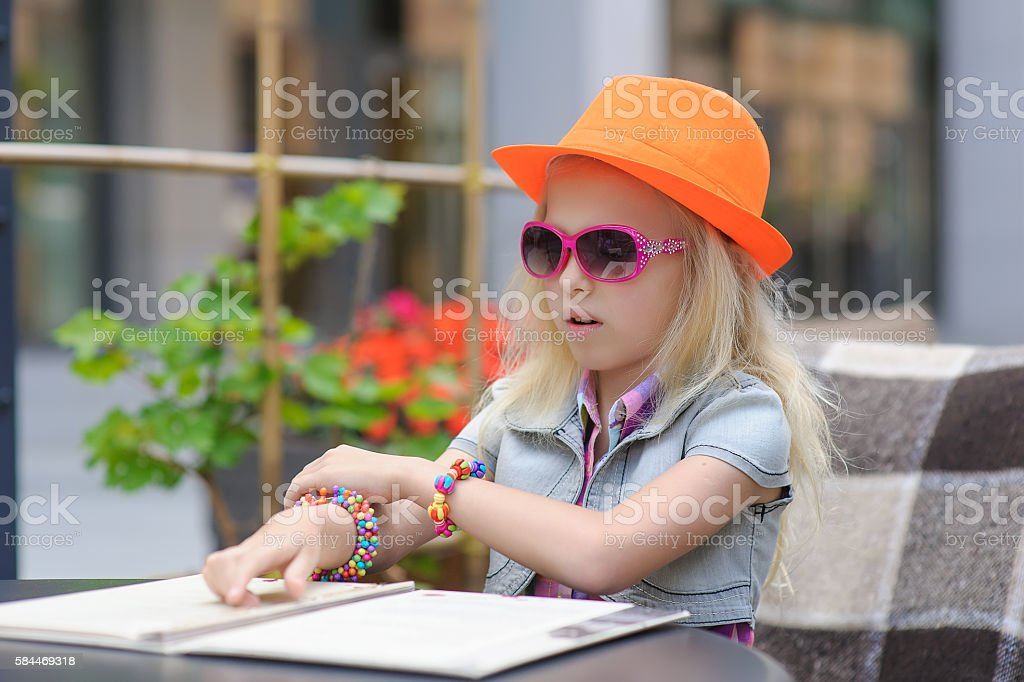 Pretty child reading menu in the cafe stock photo