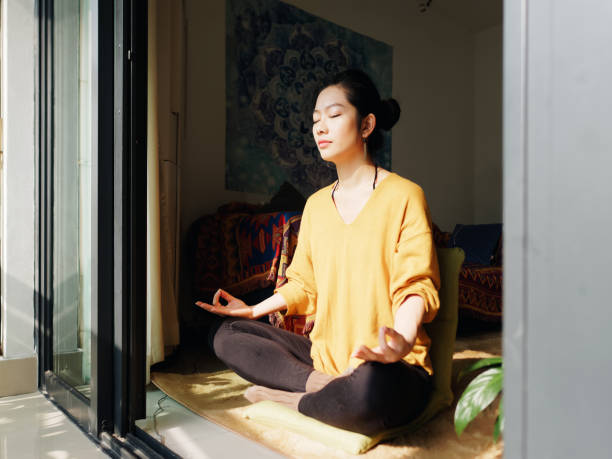 Pretty Chinese young woman meditating at home, sitting on floor with furry cushion in sun light, exercise, Lotus pose, prayer position, namaste, working out, Feeling peace and wellness concept. stock photo