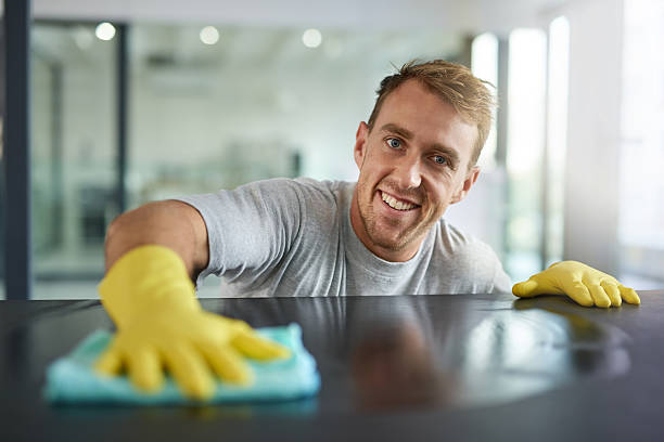 Pretty clean right? Portrait of a young man wiping off the surfaces in an office cleaner stock pictures, royalty-free photos & images