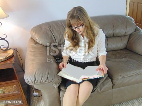 pretty co-ed studying a textbook with glasses