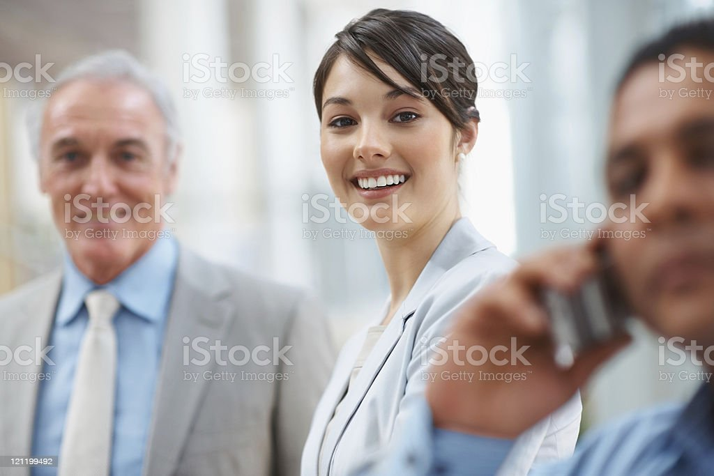 Pretty confident business executive with her colleagues at work stock photo