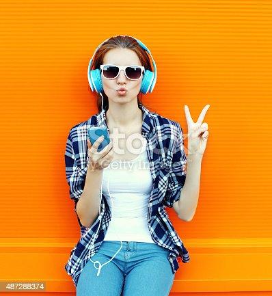istock Pretty cool girl having fun and listens music in headphones 487288374
