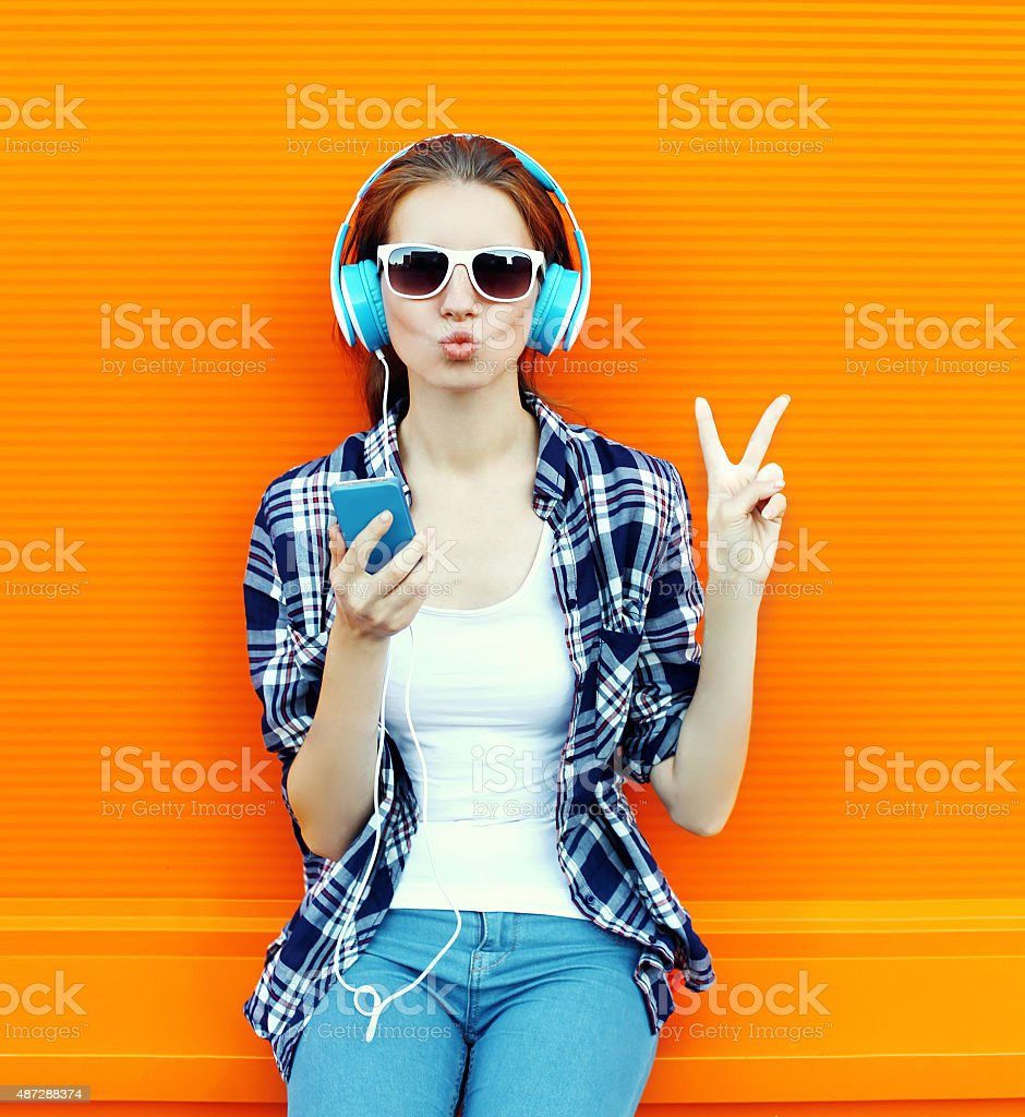 Pretty cool girl having fun and listens music in headphones stock photo