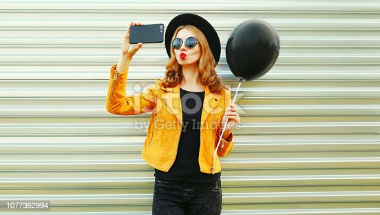 istock Pretty cool girl taking selfie picture by smartphone blowing red lips holding black helium air balloon in round hat, yellow jacket on metal wall background 1077362994
