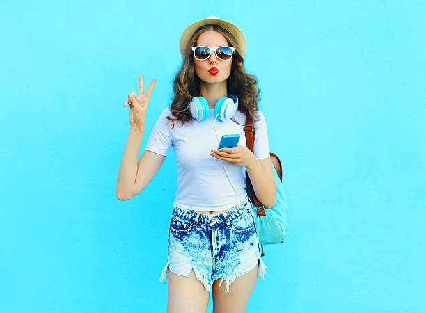 pretty cool woman listens music and using smartphone over colorf - sommermode stock-fotos und bilder