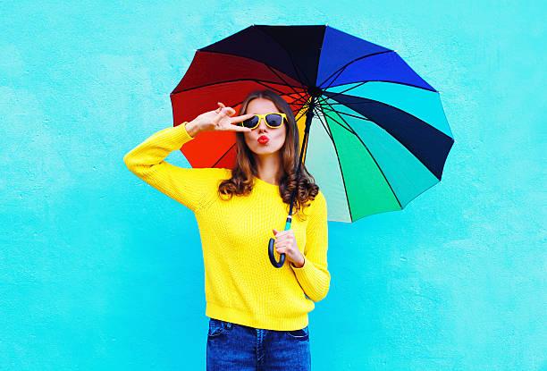 pretty cool woman with colorful umbrella in autumn over blue – Foto