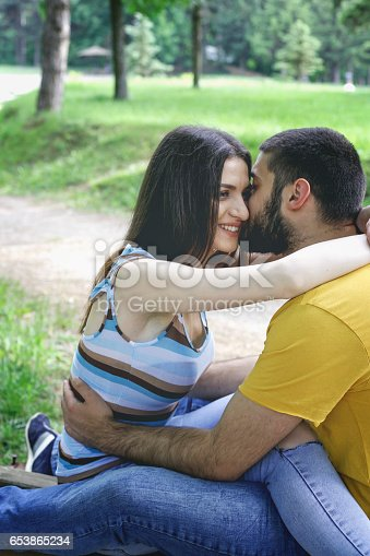 505067918 istock photo Pretty couple hugging and flirting in an urban park 653865234