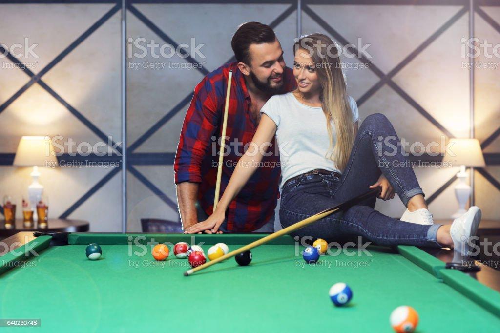 Pretty couple playing billards stock photo