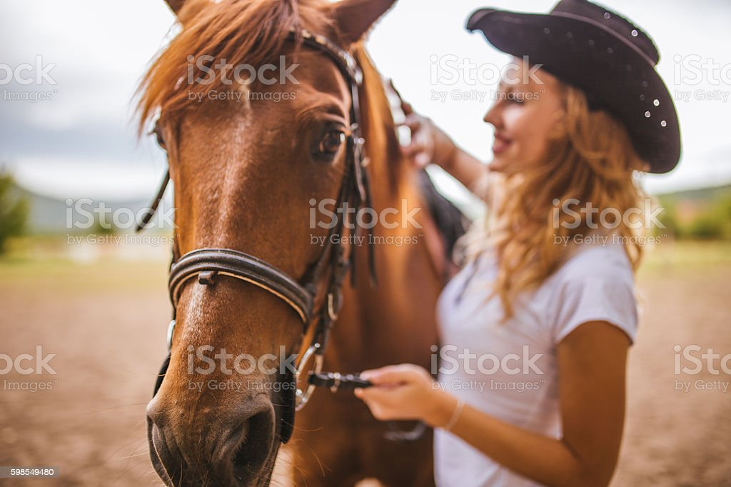 Pretty cowgirl with her horse stock photo