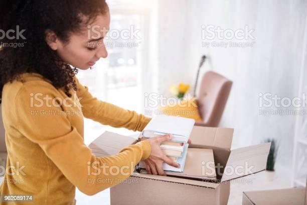 Pretty curly girl fitting books into the box picture id962089174?b=1&k=6&m=962089174&s=612x612&h=95g8p83jwspftxibnpmkkdxrnqhsr5 oslzno6dhqgq=
