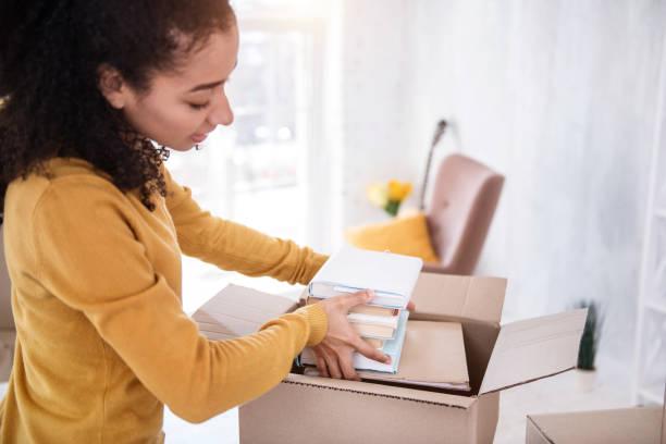 pretty curly girl fitting books into the box - oggetti personali foto e immagini stock