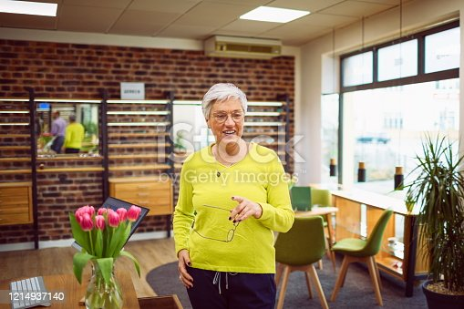 Pretty customer with short silver hair is looking for new glasses from the optician