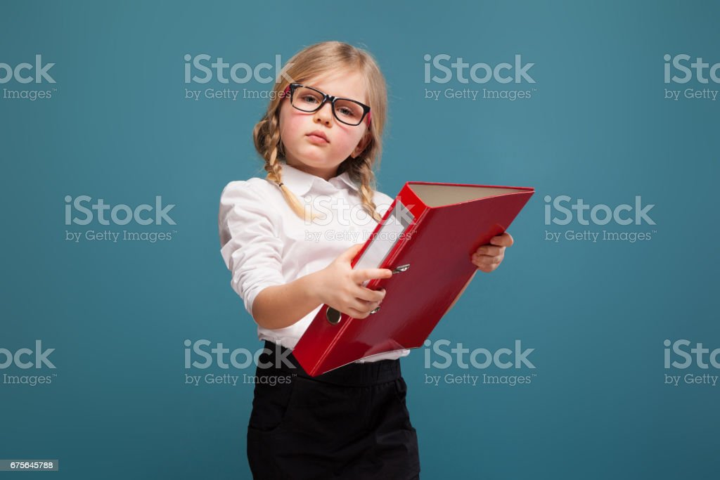 Pretty, cute little girl in white shirt, glasses and black trousers hold red paper folder royalty-free stock photo