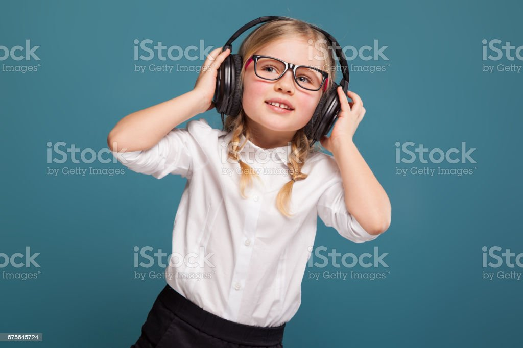 Pretty, cute little girl in white shirt, glasses, black trousers and headphones royalty-free stock photo