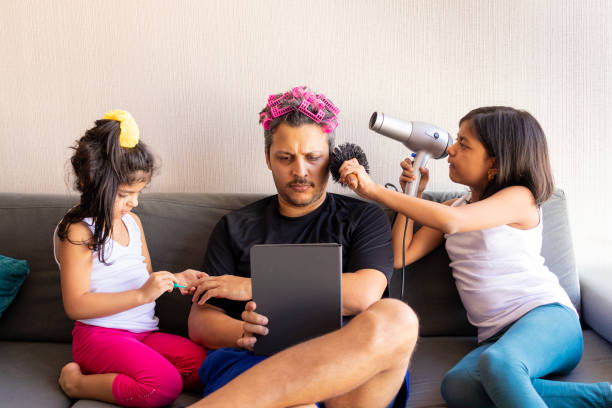 Pretty daughters are painting the nails and combing the hair of their handsome young father Pretty daughters are painting the nails and combing the hair of their handsome young father fathers day stock pictures, royalty-free photos & images