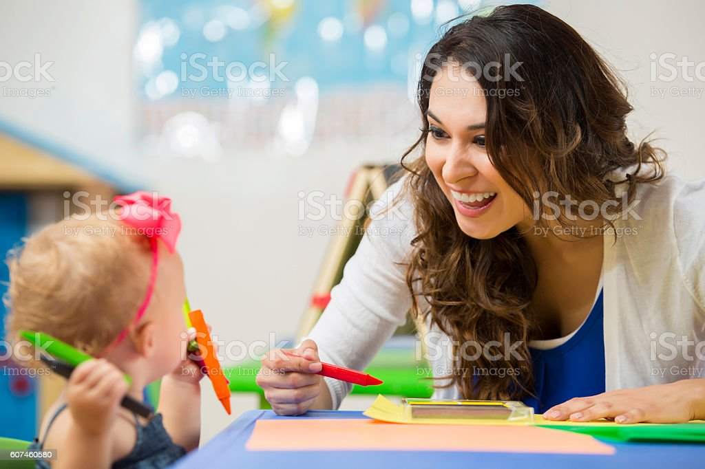 Pretty daycare teacher helps toddler with art project stock photo