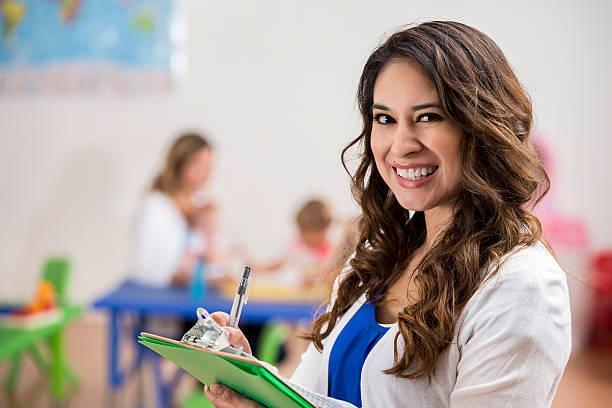pretty daycare teacher smiles confidently - erzieherin stock-fotos und bilder