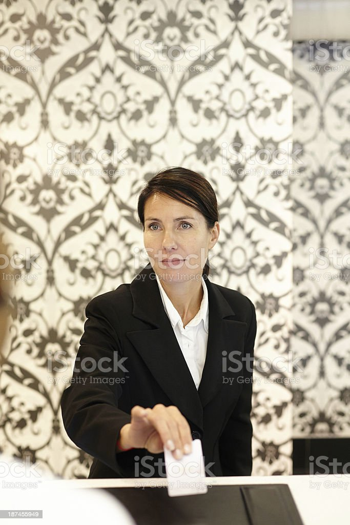 Pretty desk clerk checking a guest in at hotel stock photo