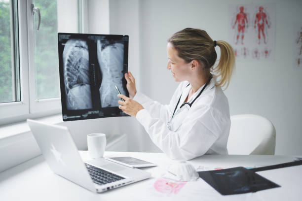 pretty doctor discusses X-ray image online with her patient stock photo