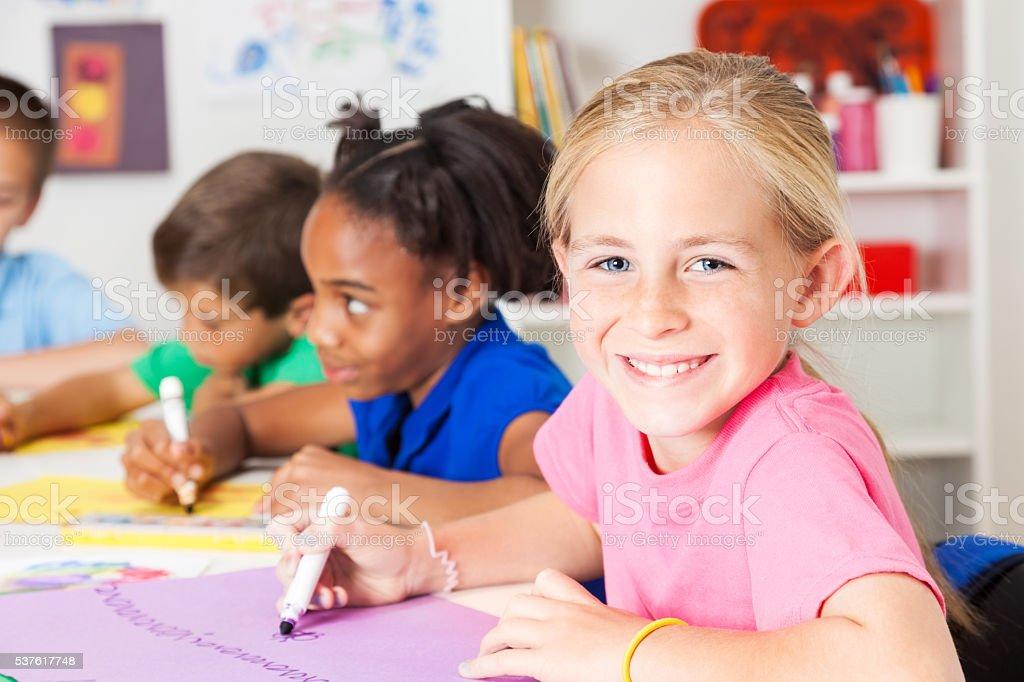 Hermosa estudiante de escuela primaria en clase de arte de colores - foto de stock