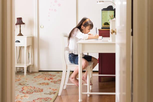 Pretty Eurasian girl doing homework in her bedroom stock photo