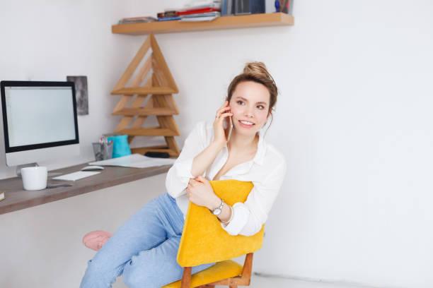 ziemlich europäischen blonde frau nutzt moderne handy, telefonieren mit handy glücklich aussehen, sitzt am arbeitsplatz. der kreative designer im büro mit digitalen geräten - telefonschrank stock-fotos und bilder