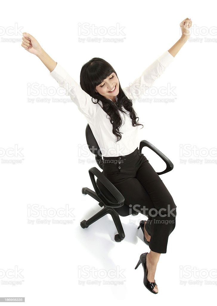 Pretty excited young woman sitting on chair celebrating victory stock photo