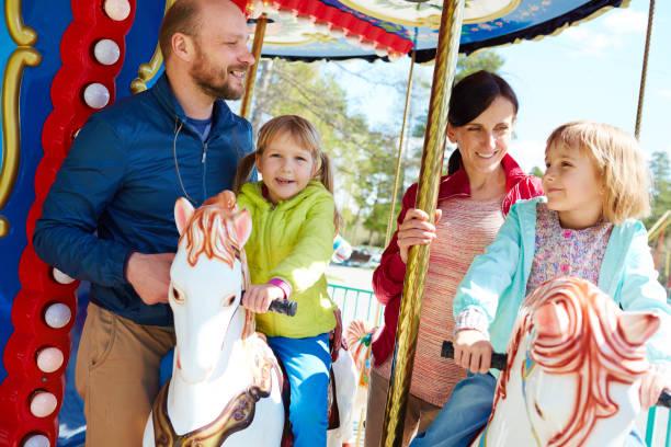 Pretty family having fun on carousel stock photo