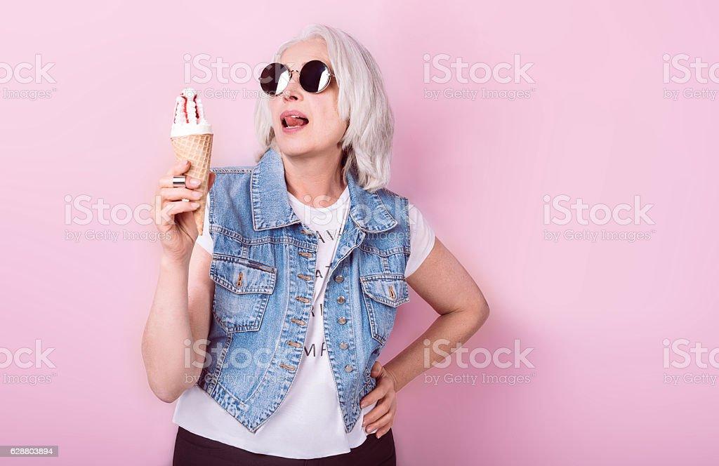 Pretty fanny senior woman holding icecream. stock photo