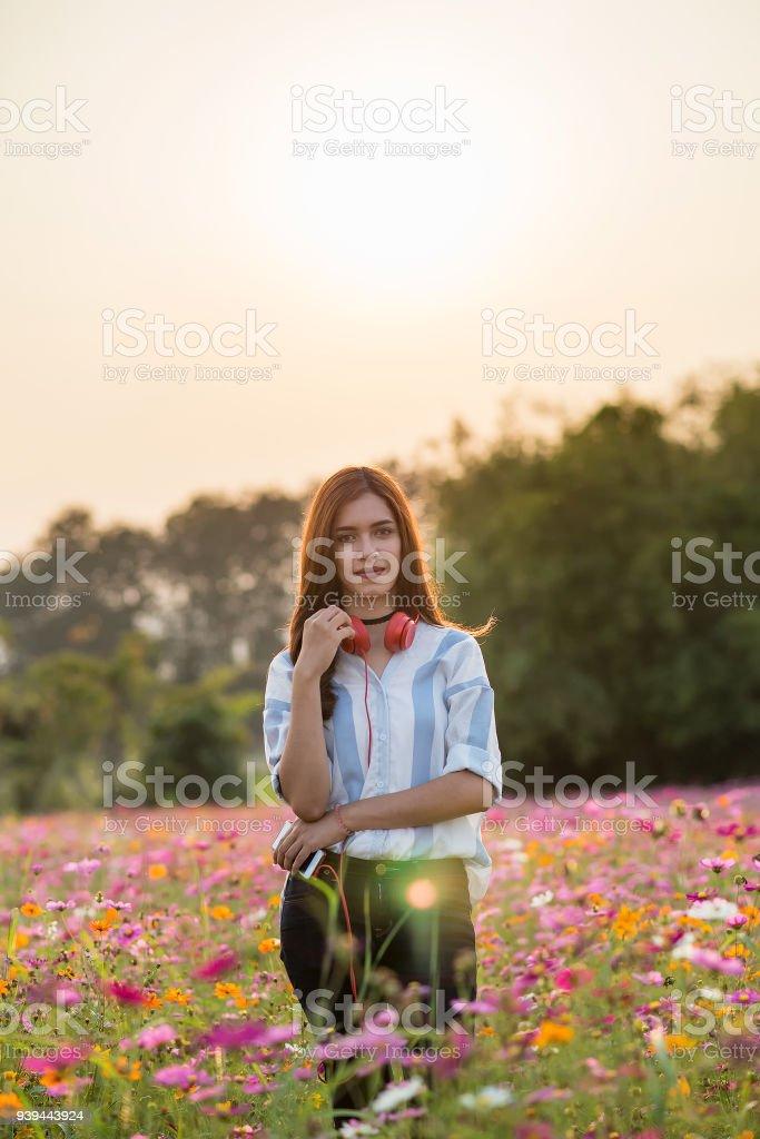 Chica cool de moda bonita escuchando música en auriculares rojo en el campo de flores. - foto de stock