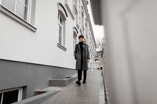 627398448 istock photo Pretty fashionable young man model in a gray elegant plaid coat with stylish hairstyle in autumn trendy boots walks near a vintage wall. Handsome modern guy in the city. Youth seasonal menswear. 1199258602