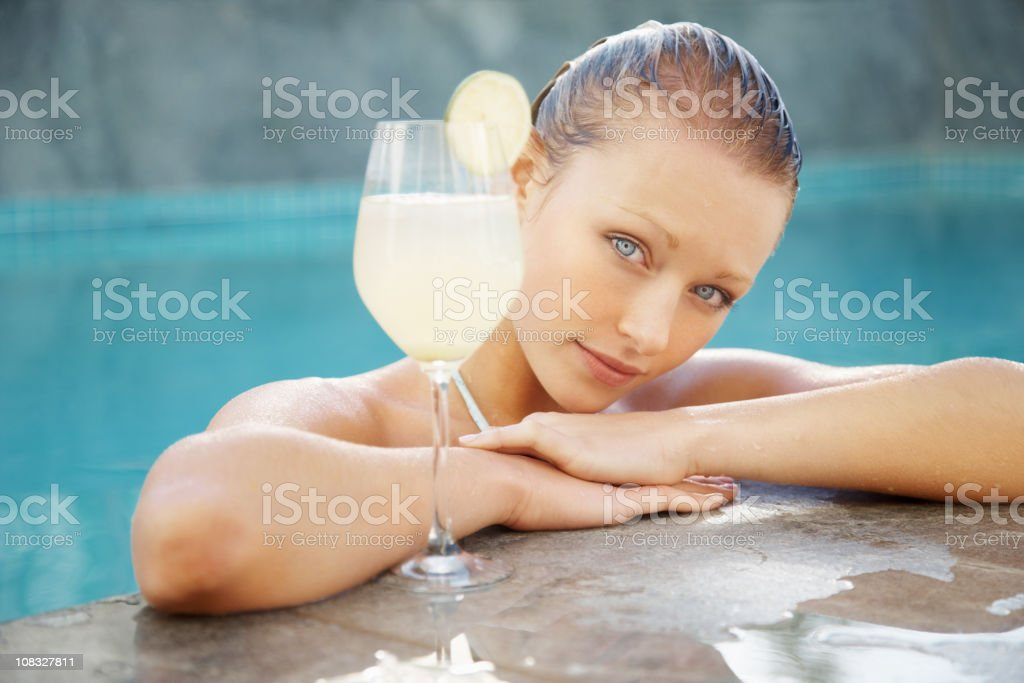 Pretty female at the edge of pool with a cocktail royalty-free stock photo