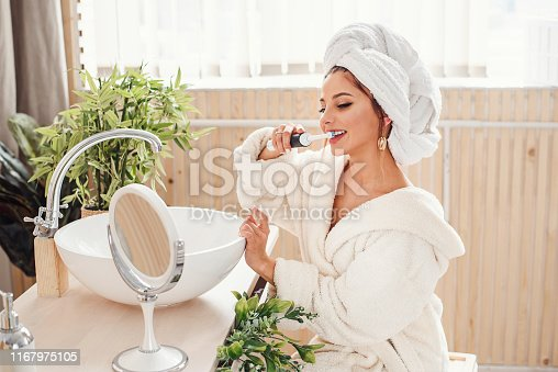 istock Pretty female brushing her teeth in front of mirror. 1167975105