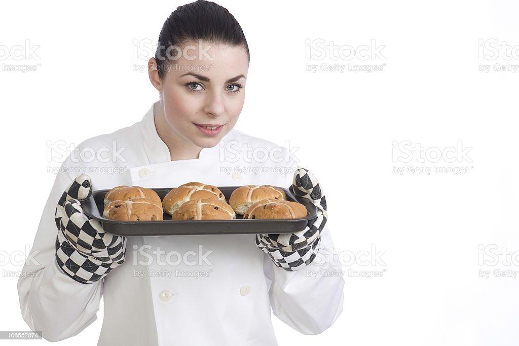 Pretty female chef cooks Hot Cross Buns royalty-free stock photo