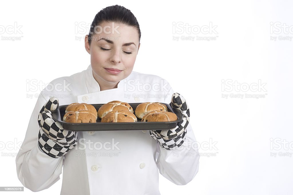Pretty female chef smells her freshly baked Hot Cross Buns royalty-free stock photo
