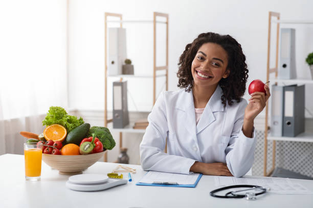 Pretty female dietologist holding apple in her hand and smiling stock photo