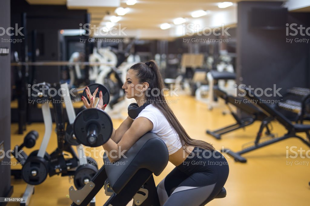 Pretty female doing weight lifting at gym stock photo