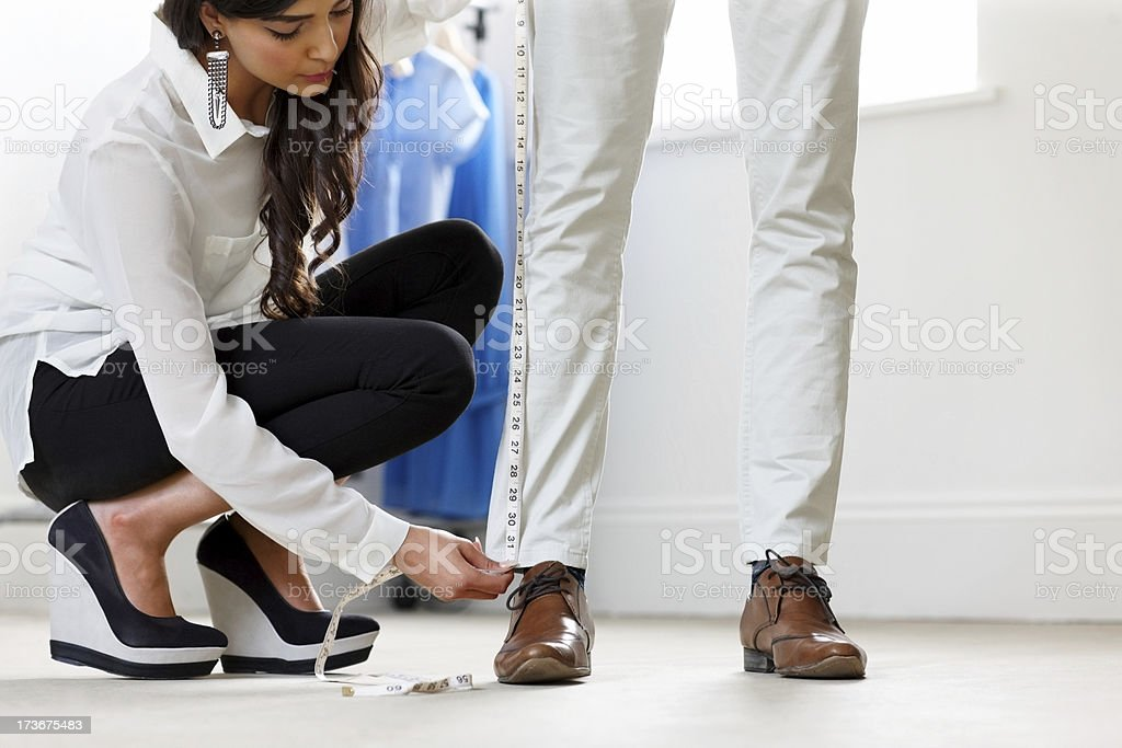 Pretty female dressmaker measuring height of a man's pants stock photo