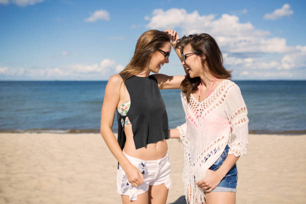 Pretty female friends looking at each other laughing on beach stock photo